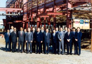 創業メンバーと建築中のつくば本社の写真(1985年)